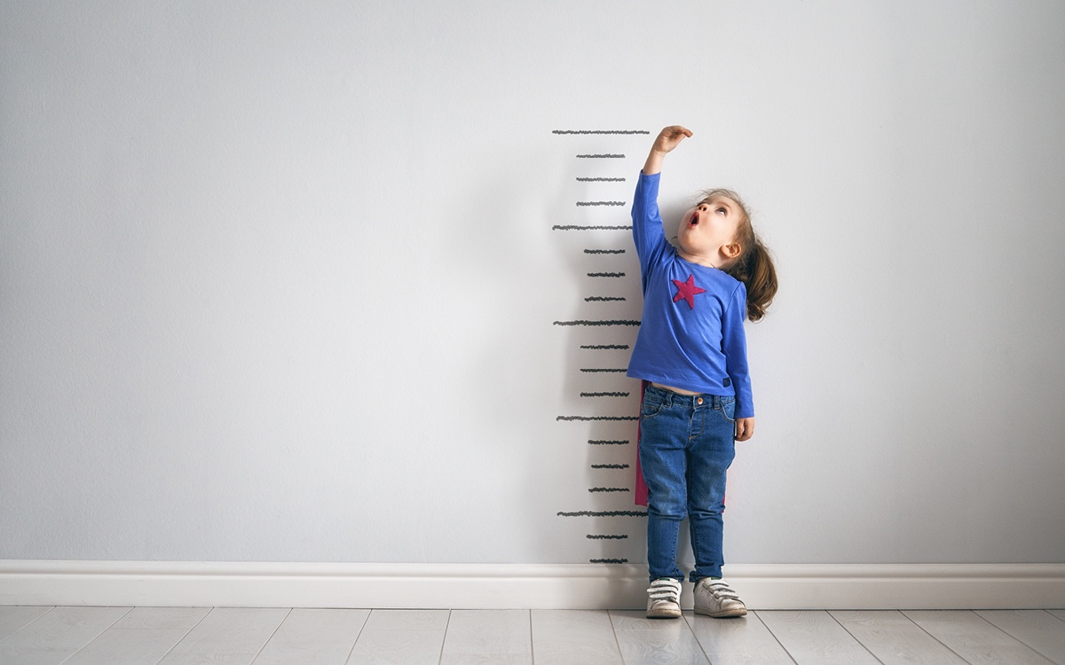 Girl in front of a measuring scale.